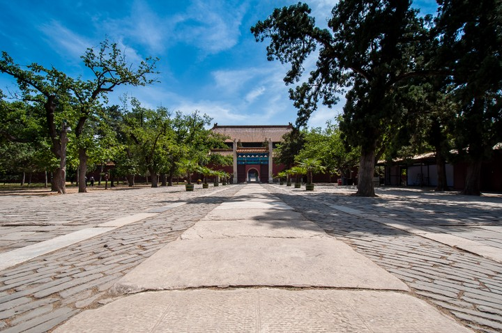 Wide paved path lined with trees at the Emperors Tomb in Beijing