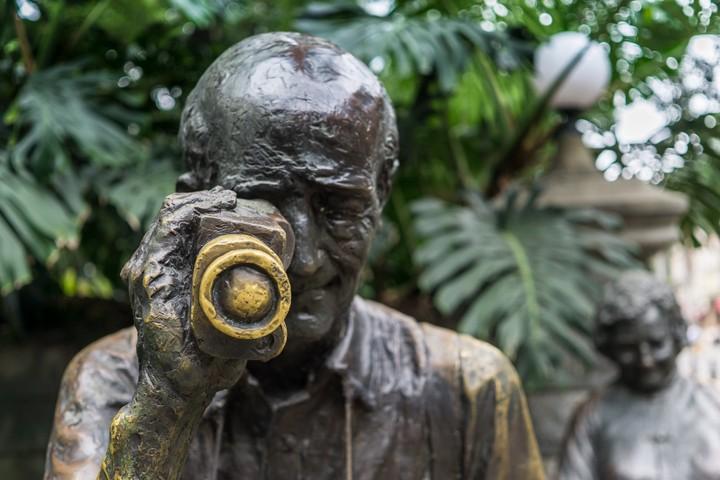 Bronze statue of man holding camera