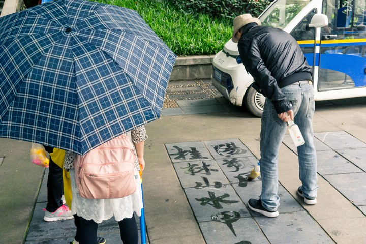 Person drawing Chinese characters with water