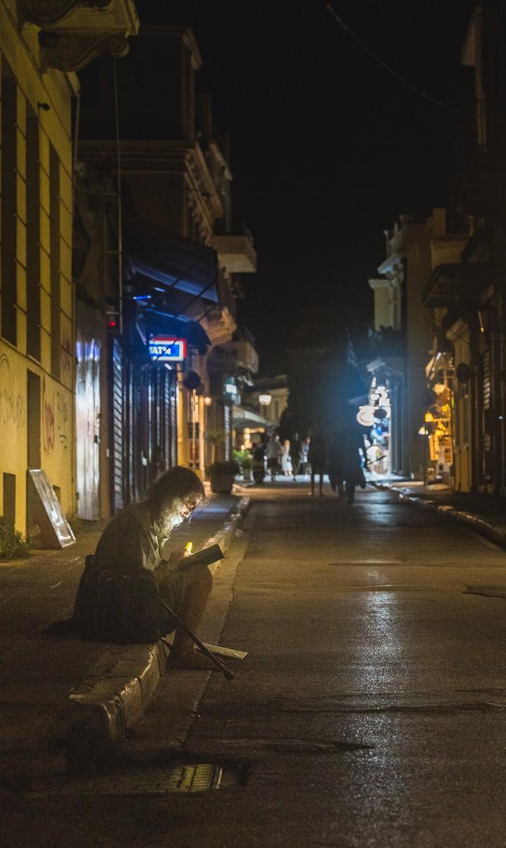 Man reading book on sidewalk in the dark