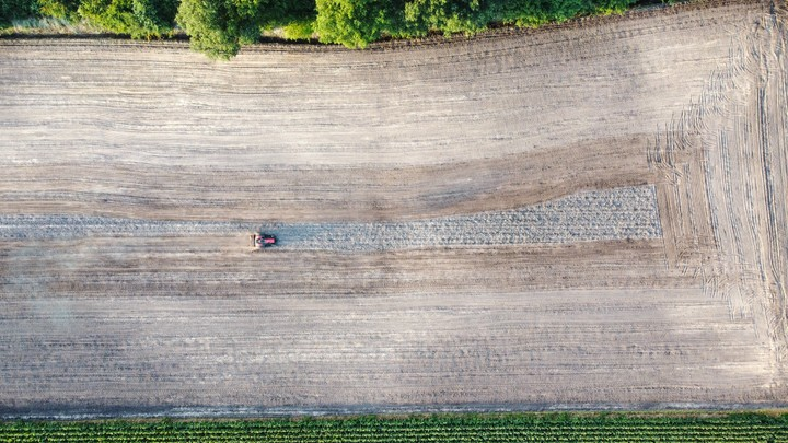 Drone shot of tractor tending to fields
