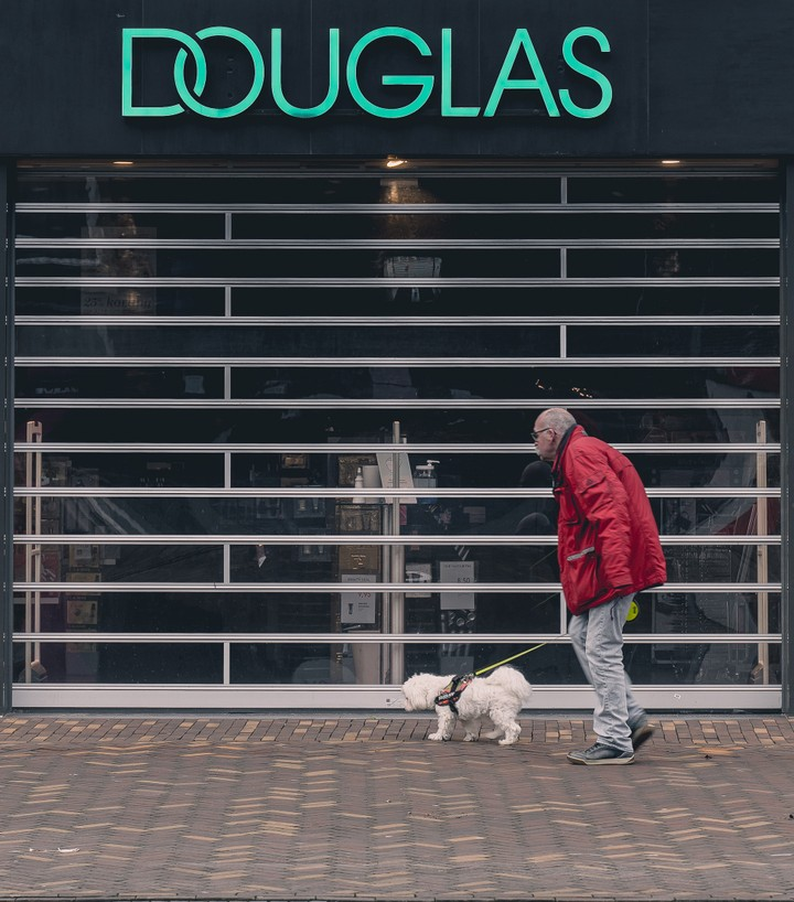 Man with dog walking in front of a shop called Douglas