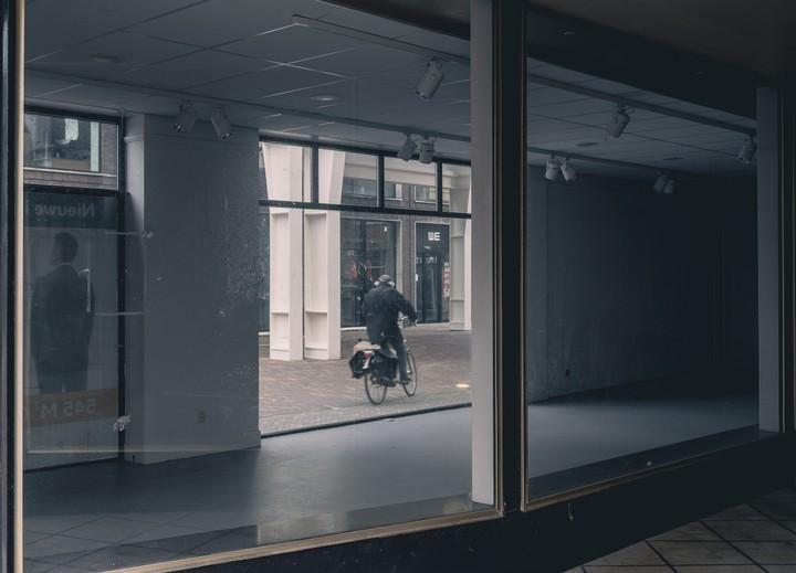 Man riding bike taken through window