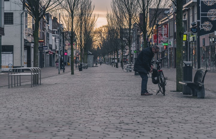 Hoofdstraat in Veenendaal Man putting stuff into a bag