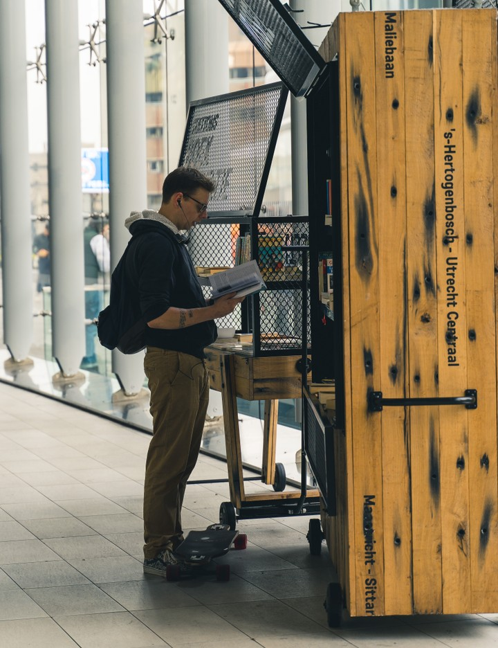 Person reading book at Utrecht Central Station