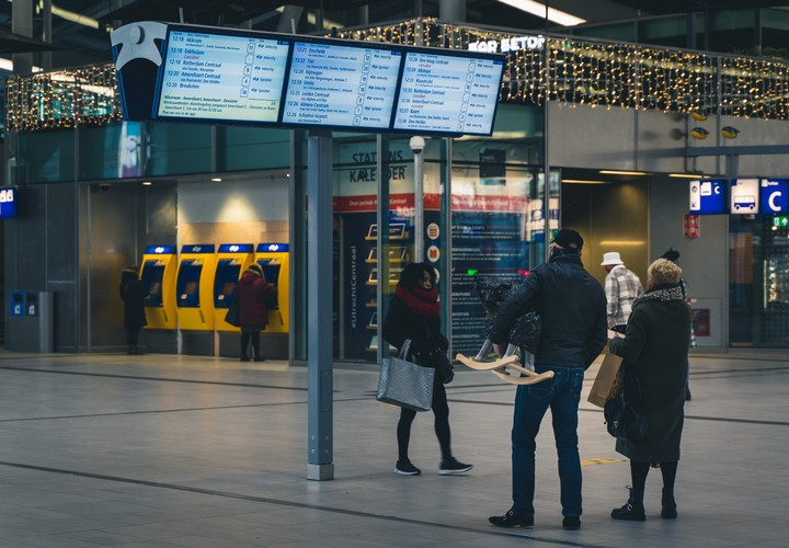 People looking at departue board at Utrecht Central Station
