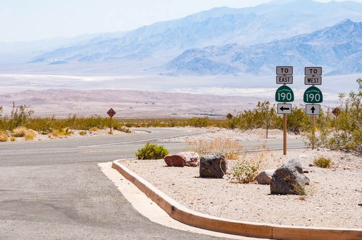 View of Death Valley National Park showing signs pointing to 190 East and West
